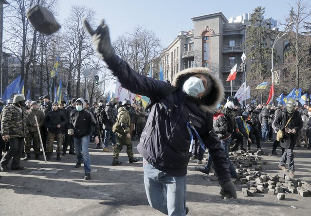 An anti-government protester  throw a stone during clashes with riot police outside Ukraine's parliament in Kiev, Ukraine, Tuesday, February 18, 2014. Thousands of angry anti-government protesters clashed with police in a new eruption of violence following new maneuvering by Russia and the European Union to gain influence over this former Soviet republic. (Photo by Efrem Lukatsky/AP Photo)