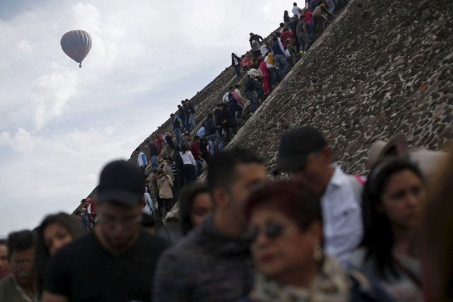 A hot air balloon floats past people standing in line to climb the Pyramid of the Sun and welcome the spring equinox in the pre-hispanic city of Teotihuacan, on the outskirts of Mexico City, Mexico, March 20, 2016. (Photo by Edgard Garrido/Reuters)