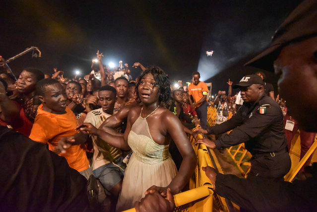 Ivorian police officers of the Anti-Riot Brigade (BAE) contain the crowd during a performance by French rapper Okou Armand Gnakouri known as Kaaris during the Festival of Urban Music of Anoumabo (Femua) in Abidjan on April 28, 2019. The performance of French-Ivorian rapper Kaaris at the Festival of Urban Music of Anoumabo (Femua) in Abidjan escalated into violence after a crowd surge, causing some minor injuries, according to an AFP journalist at the concert. (Photo by Sia Kambou/AFP Photo)
