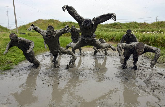 Paramilitary policemen jump during a training session in muddy water at a military base in Chuzhou, Anhui province, China, May 13, 2015. (Photo by Reuters/China Daily)