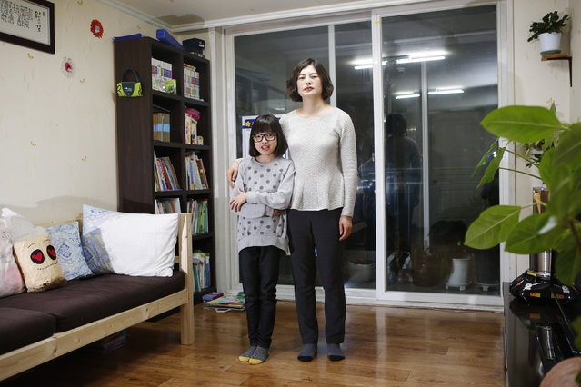 Kang Hyun-jeong, 43, and her daughter Yoo Ha-min, 11, pose for a photograph in the living room of their apartment in Seoul February 21, 2014. Kang Hyun-jeong works in accounts. She says that she started working in her senior year of high school, but she began a business degree in 1999 at the Korea National Open University because she wanted to study more. She juggled work and classes and graduated eight years later in 2007. (Photo by Kim Hong-Ji/Reuters)