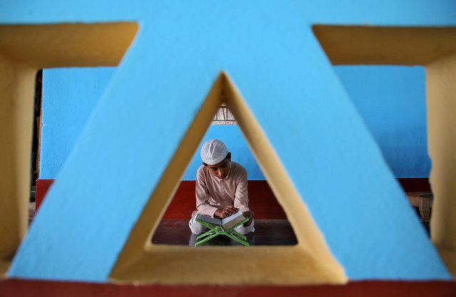 A Muslim boy reads the Koran inside a mosque on the first day of the holy fasting month of Ramadan on the outskirts of Agartala, India on May 7, 2019. (Photo by Jayanta Dey/Reuters)
