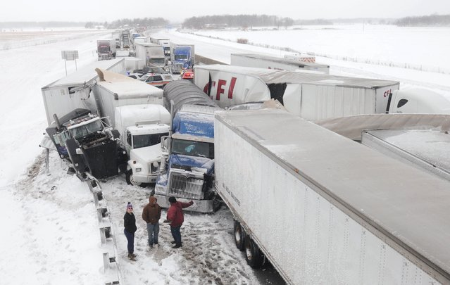 Truck drivers talk amongst themselves at the scene of an accident on the Ohio Turnpike northeast of Clyde, Ohio after more than 50 vehicles crashed, Wednesday, March 12, 2014. (Photo by Jonathon Bird/AP Photo/Fremont News-Messenger)