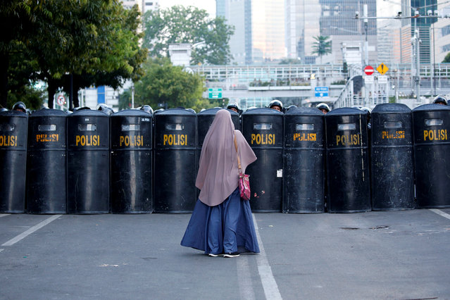 A woman stands in front of a riot-police's barricade after a riot outside Indonesia's Election Supervisory Agency (Bawaslu) headquarters following the announcement of last month's presidential election results in Jakarta, Indonesia, May 24, 2019. (Photo by Willy Kurniawan/Reuters)