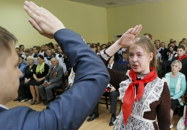 A girl, wearing a red neckerchief, a symbol of the Young Pioneer Organisation, salutes during a ceremony for the inauguration of 45 newly adopted members on the day of its anniversary at school-lyceum number 12 in the Siberian city of Krasnoyarsk, Russia, May 19, 2015. (Photo by Ilya Naymushin/Reuters)
