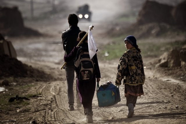 """Iraqis carry belongings as they flee Mosul on March 1, 2017, during an offensive by security forces to retake the western parts of the city from Islamic State (IS) group fighters. At least 26,000 people have fled in the 10 days since Iraqi forces launched the push to retake west Mosul, where jihadists put up """"fierce"""" resistance. (Photo by Aris Messinis/AFP Photo)"""