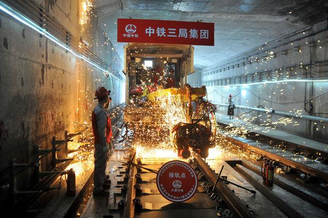 Workers on the tracks of a metro line under construction in Guangzhou, China on June 5, 2019. (Photo by Reuters/China Stringer Network)