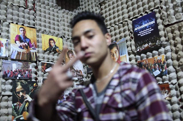 Afghan rapper Mahmoud Hejran shows his band's symbol as he poses for a photograph at his apartment, which is used as a music studio, in Kabul March 3, 2014. (Photo by Morteza Nikoubazl/Reuters)