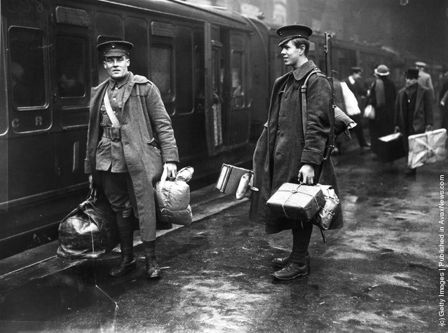 1914: Two soldiers on the concourse at Victoria station, London, about to leave for the front line. They are carrying parcels full of food and other provisions