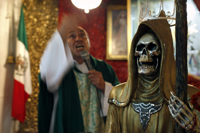 "In this February 19, 2017 photo, a statue of the Death Saint stands inside Mercy Church as Juan Carlos Avila Mercado gives a service, on the edge of Mexico City's Tepito neighborhood. ""She chooses them and has always been with us"", said Avila, who says he is a Catholic priest, but who is not listed among the archdiocese's priests. ""We are born and we die with death"". (Photo by Marco Ugarte/AP Photo)"