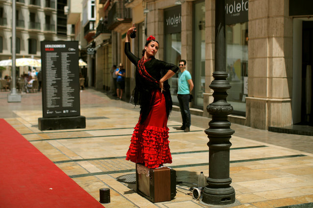 A woman, wearing a traditional Sevillana dress, performs as she asks for alms in downtown Malaga, Spain, April 28, 2016. (Photo by Jon Nazca/Reuters)