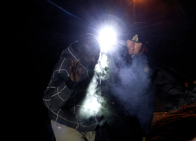 "A man is told to stop by a Royal Canadian Mounted Police (RCMP) officer after he illegally crossed the U.S.-Canada border leading into Hemmingford, Quebec, Canada, March 20, 2017. A Sudanese man hopped out of his taxi with a duffle bag slung around his shoulder just before daybreak, as he headed for the U.S. – Canadian border. Within a matter of seconds, the man, who sought to brave the negative 6 degrees Celsius (21 degrees Fahrenheit) weather, was confronted by a female Royal Canadian Mounted Police (RCMP) officer who shined her flashlight on him as he crossed into Hemmingford, Quebec from Champlain, New York. Dressed in a checkered sweatshirt, pants and snow boots, the Sudanese traveler is one of several people looking to build a life in Canada as U.S. President Donald Trump vows a sharpened crackdown on America's illegal immigrants. ""Stop, you have to stop"", the officer insisted, grabbing his arm. Over and over again, the man, who did not provide his name, muttered as if speaking to himself: ""I need to be safe, I need to be safe, I just want to be safe"". He kept walking, desperately trying to plow past the officer. He only stopped when the officer told him, almost empathetically: ""You're in Canada already. You're in Canada. You're here"". Now, with no reluctance, he put his hands in the air as she told him he was under arrest and that he had entered Canada illegally. The exchange lasted all of four minutes. (Photo by Christinne Muschi/Reuters)"