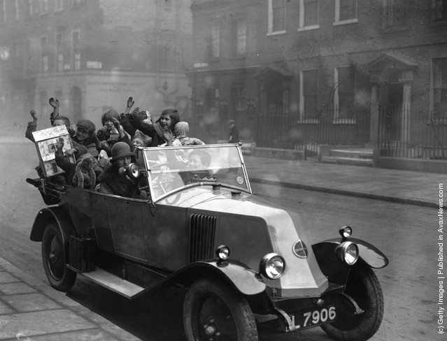 1925: A car full of 'Ragged Children', who have received Christmas presents