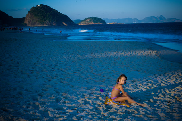 """""""Girl in Copacabana Beach"""". In the end of the afternoon I could capture the last moments of the pale light of the sun bathing my daughter, while she was playing on the beach. While the background had a predominant blue light, the last rays of the sun enlighted the girl. WB adjusted to Sun Light. Photo location: Copacabana Beach, Rio de Janeiro. (Photo and caption by Elvio Santos/National Geographic Photo Contest)"""