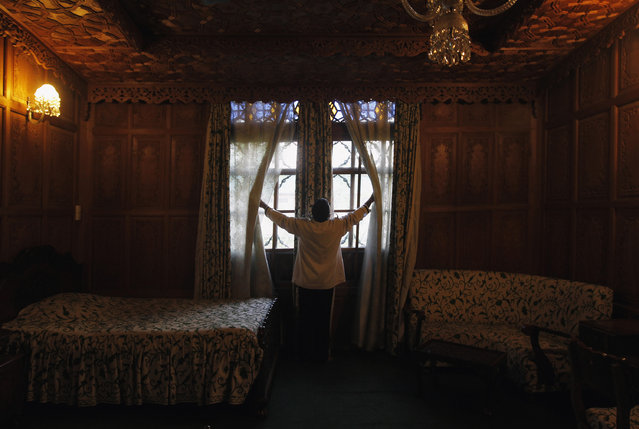 A waiter adjusts the curtains in a room of a houseboat in Srinagar June 8, 2012. For nearly a century, hand-carved houseboats bobbing on a placid lake drew millions of visitors including George Harrison, businessman Nelson Rockefeller and actress Joan Fontaine to the stunningly beautiful Himalayan region of Kashmir. (Photo by Fayaz Kabli/Reuters)