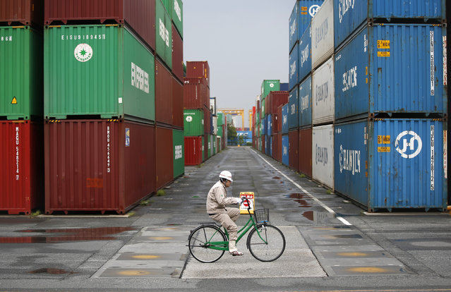 A worker rides a bicycle in a container area at a port in Tokyo April 21, 2014. Japan suffered its worst annual trade deficit in March as exports growth slowed to its weakest in a year, suggesting a rapid loss of economic momentum that may prompt policy makers into early action as a national sales tax hike puts more strain on growth. (Photo by Toru Hanai/Reuters)