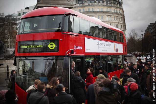 Reporters and television crews surround a new prototype red double decker bus in Trafalgar Square