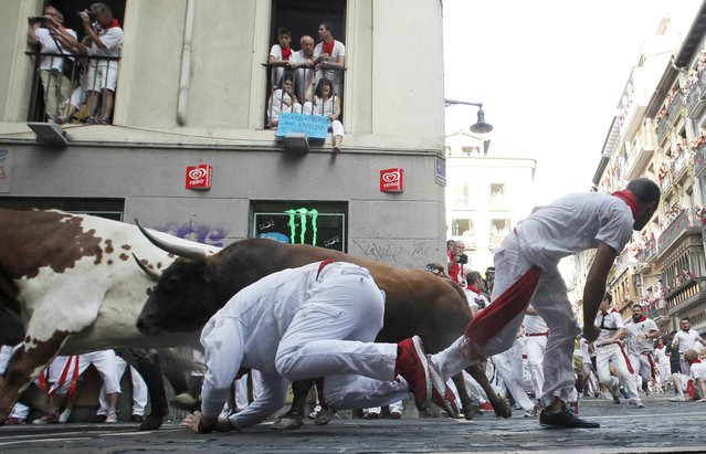 A runner falls next to a Jandilla fighting bull at the Mercaderes curve during the first running of the bulls of the San Fermin festival in Pamplona, northern Spain, July 7, 2015. (Photo by Susana Vera/Reuters)