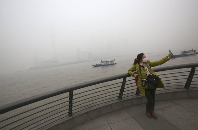 A tourist with a protective mask takes her self portrait at the Bund under heavy haze in Shanghai, China, Friday, December 6, 2013. Shanghai authorities ordered schoolchildren indoors and halted all construction Friday as China's financial hub suffered one its worst bouts of air pollution, bringing visibility down to a few dozen meters and obscuring the city's spectacular skyline. (Photo by Eugene Hoshiko/AP Photo)