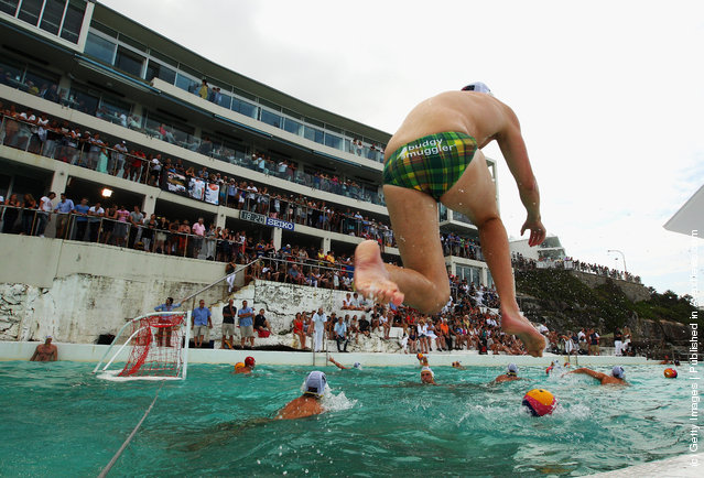 An Australian team member jumps into the water during warm-up before the Water Polo by the Sea match between Australia and the United States of America at at Bondi Icebergs on Bondi Beach