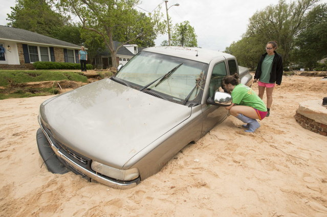 Reagan Strom (L) 15, and her friend Natasja Ugarte, 16, view a pickup truck that became buried in sand and mud after the road was washed away in their Cordova Park neighborhood in Pensacola, Florida, May 1, 2014. The remnants of the storm that dumped up to 11 inches (28 cm) of rain in the Florida Panhandle on Wednesday had moved into the Atlantic Ocean by early Thursday, said Dan Petersen, a National Weather Service meteorologist. (Photo by Michael Spooneybarger/Reuters)
