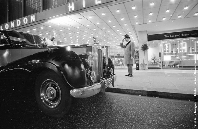 1965: A doorman salutes a guest arriving at the Hilton Hotel, London, in a Rolls Royce