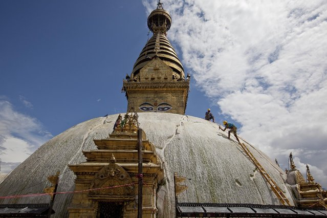 Nepalese laborers work on reconstructing the earthquake damaged Swayambhunath Stupa in Kathmandu, Nepal, Thursday, July 9, 2015. The director of U.N. humanitarian operations urged Nepal on Wednesday to fast-track clearance and waive taxes on aid shipments which are delaying desperately needed assistance getting to 500,000 people who urgently need food and 100,000 households that still require shelter following two devastating earthquakes. (Photo by Niranjan Shrestha/AP Photo)