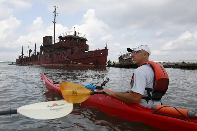 "Decaying vessels are seen as John Pagani, owner of Kayak East, paddles by during the ""Graveyard of Ships"" kayak tour on the Arthur Kill, New York, July 7, 2015. Bright colored kayaks bobbed around the rotted hull of a World War II submarine chaser that was rusted into a ghostly shell and lapped by water as salty as tears. (Photo by Shannon Stapleton/Reuters)"
