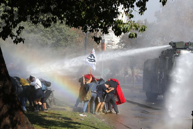 Student demonstrators take cover from a jet of water released from a riot police vehicle during a demonstration to demand changes in the Chilean education system, in Santiago May 8, 2014. Thousands of students marched through the Chilean capital on Thursday for the first time since President Michelle Bachelet took power, ratcheting up the pressure on her to fulfill her campaign pledges to overhaul education in the country. (Photo by Ivan Alvarado/Reuters)