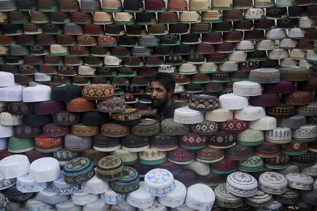 A Pakistani vendor waits for customers to sell caps in Karachi, Pakistan, Wednesday, June 17, 2015. Muslims throughout the world mark the month of Ramadan, the holiest month in the Islamic calendar, with dawn to dusk fasting. It is customary in some countries to wear caps when offering prayers in mosques. (Photo by Shakil Adil/AP Photo)