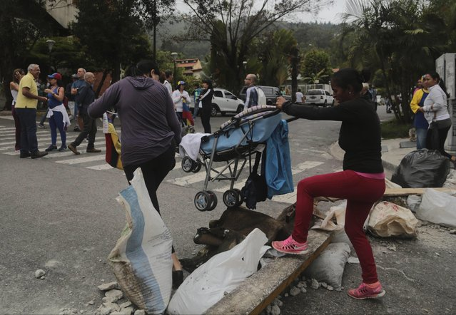 A man helps a woman cross a barricade set up by residents blocking streets in El Hatillo's municipality near Caracas, Venezuela, Tuesday, May 2, 2017. Caracas residents blocked streets with trash bags, broken concrete and twisted metal Tuesday to protest the president's bid to rewrite the constitution amid a deepening political crisis. (Photo by Fernando Llano/AP Photo)