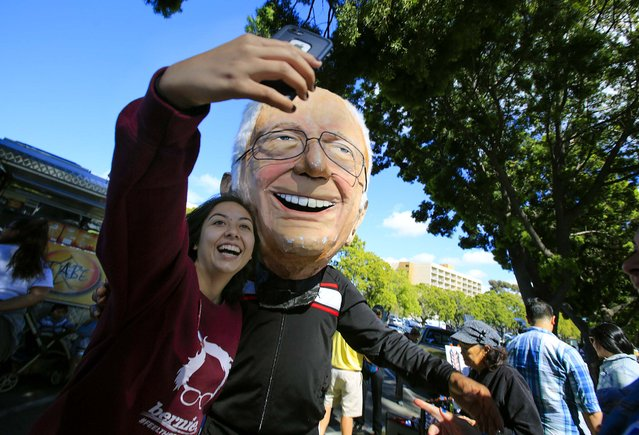 Bernie Sanders supporter Arely Ramos of Chula Vista takes a self with Mike Johnson of Linda Vista, wearing a paper mache Bernie Sanders head while they wait for the doors to the rally in Kimball Park to open Saturday, May 21, 2016 in National City, Calif. (Photo by Howard Lipin/The San Diego Union-Tribune via AP Photo)