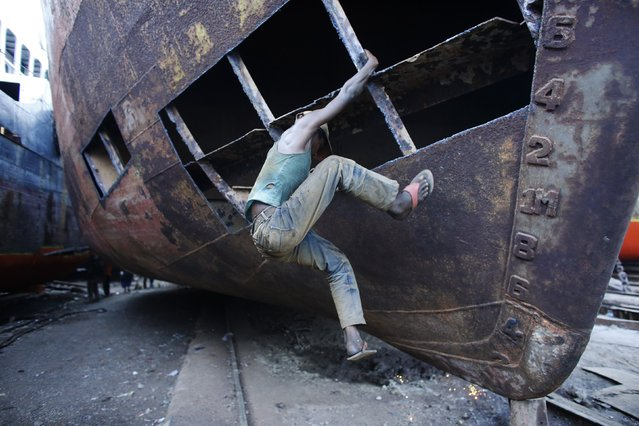 A labourer climbs out of a half-made ship as he leaves after finishing his work at a shipyard by the river Buriganga, on the outskirts of Dhaka May 19, 2014. (Photo by Andrew Biraj/Reuters)