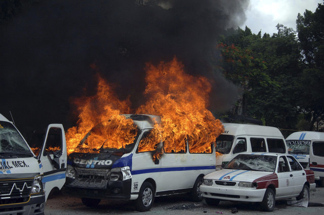 A taxi bus burns after a fight broke out between rival taxi unions fighting for permits in the city of Chilpancingo, Mexico, Monday, July 20, 2015. Several taxi drivers were injured and dozens of vehicles were destroyed. (Photo by Alejandrino Gonzalez/AP Photo)