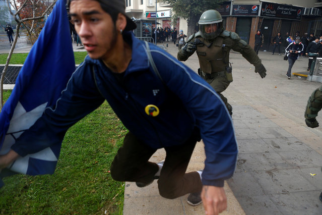 A demonstrator runs away from a riot policeman during an unauthorized march called by secondary students to protest against government education reforms in Santiago, Chile, May 26, 2016. (Photo by Ivan Alvarado/Reuters)