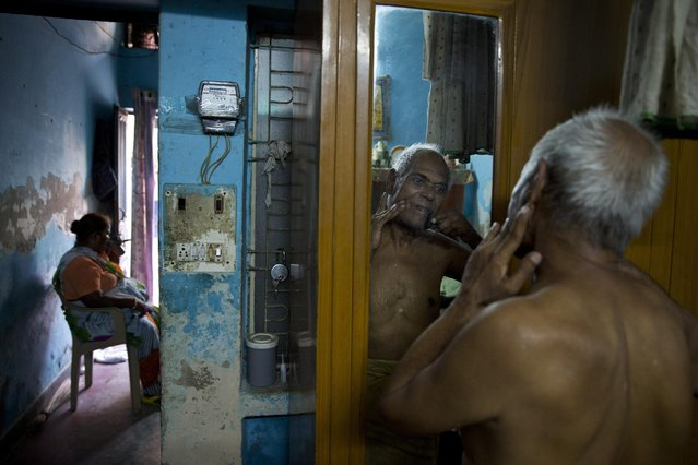 """In this June 8, 2015 photo, Omkarnath, who goes by the name """"Medicine Baba"""", shaves without cream or foam as he gets ready for the day at his rented accommodation at a fetid slum in New Delhi, India. (Photo by Saurabh Das/AP Photo)"""