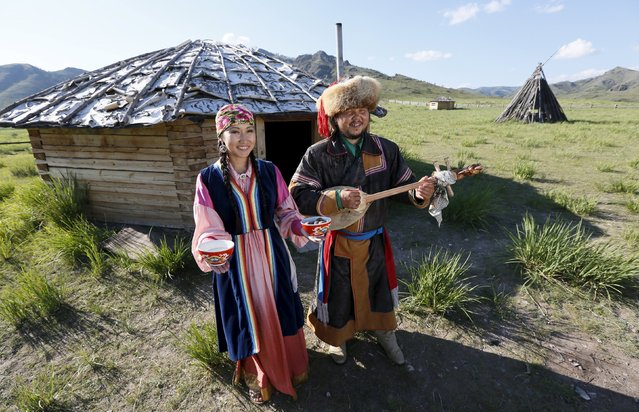 Members of national folklore and ethnographic groups and employees of a museum-preserve participate in the reconstruction of daily life and traditional holidays celebrated by indigenous population of the Republic of Khakassia during a demonstration for visitors outside a traditional wooden yurt near Kazanovka village, southwest of the city of Abakan, Russia, July 24, 2015. (Photo by Ilya Naymushin/Reuters)