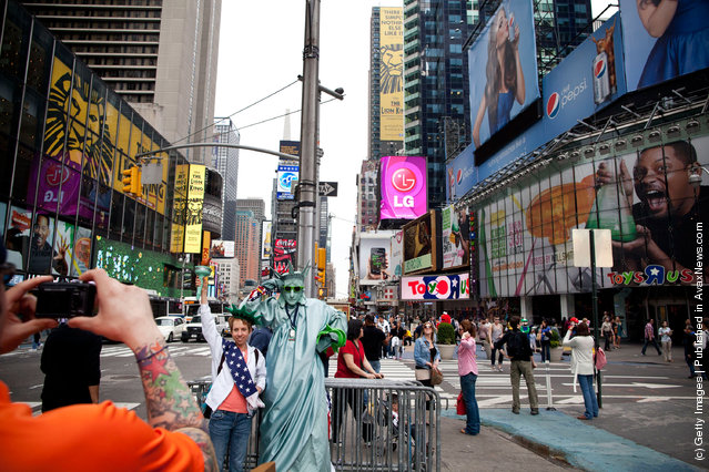 A tourist has her photo taken with a man dressed up as the Statue of Liberty in Times Square