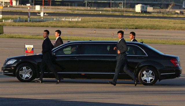 Security officers guard a limousine carrying Russian President Vladimir as he arrives at Beijing Capital International Airport to attend the upcoming military parade in Beijing, China, 02 September 2015. (Photo by Wu Hong/EPA)