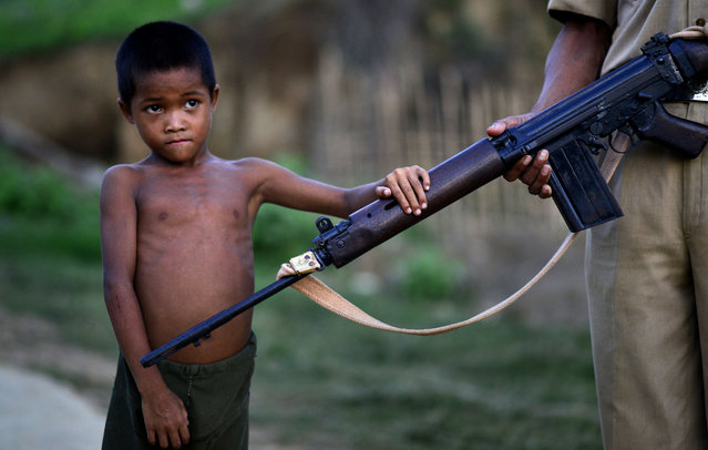 A Bru tribal boy with one of his hands placed on the gun of a security officer deployed in the Naisingpara Bru refugee relief camp, in Tripura state, India, 16 June 2014. The repatriation of the Mizoram Bru refugees will be carried out on 17 June 2014 from six Bru refugee camps who are now lodging in transit camps in neighbouring Tripura state, since they fled Mizoram in 1997 following ethnic violence. (Photo by EPA/STR)