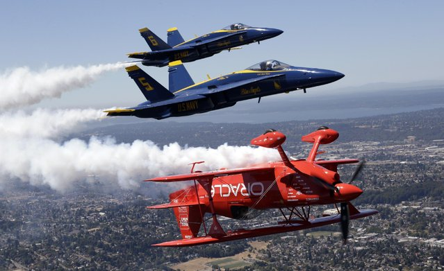 Team Oracle stunt pilot Sean Tucker, bottom, is joined in close formation by a pair of U.S. Navy Blue Angels as they trail vapor during an air show practice run in Seattle, Thursday, July 30, 2015. The Blue Angels, Tucker and a number of other aircraft will perform in the show at Seafair Weekend over Lake Washington Friday through Sunday. (Photo by Elaine Thompson/AP Photo)