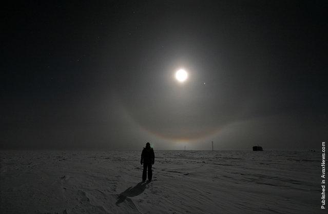 A US Antarctic Program participant enjoys a walk under a full moon at Amundsen-Scott South Pole Station on June 19, 2008