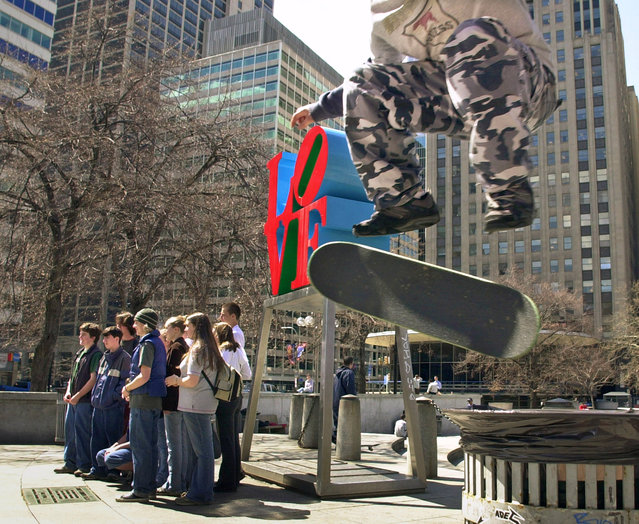In this April 1, 2002, file photo, Mike Cole, of Jenkintown, Pa., right, performs a kick-flip over a trash can with his skateboard as tourists pose for photos in front of artist Robert Indiana's sculpture in John F. Kennedy Plaza, also known as Love Park, in Philadelphia. Granite slabs from Philadelphia's famed Love Park, a skateboarding mecca though for a long stretch an illegal one, are being shipped in 2017 to the city of Malmo, Sweden, nearly 4,000 miles away, for use in construction of a skate park there. (Photo by Douglas Bovitt/AP Photo)