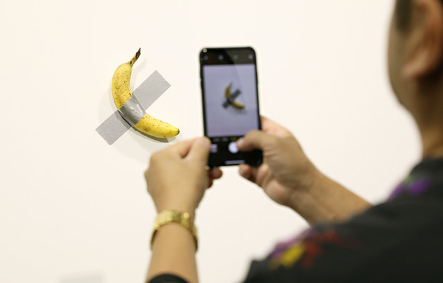 """People post in front of Maurizio Cattelan's """"Comedian"""" presented by Perrotin Gallery and on view at Art Basel Miami 2019 at Miami Beach Convention Center on December 6, 2019 in Miami Beach, Florida. Two of the three editions of the piece, which feature a banana duct-taped to a wall, have reportedly sold for $120,000. (Photo by Cindy Ord/Getty Images)"""