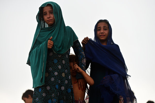Pakistani girls cry during an operation to tear down a poverty-stricken neighbourhood where Afghan refugees and Pakistani tribal people live in Islamabad on July 30, 2015. Teams of Capital Development Authority (CDA) backed by a heavy contingent of police and security personnel began tearing down the Afghan Basti area of the national capital, with angry residents responding with protests and stone throwing. (Photo by Farooq Naeem/AFP Photo)