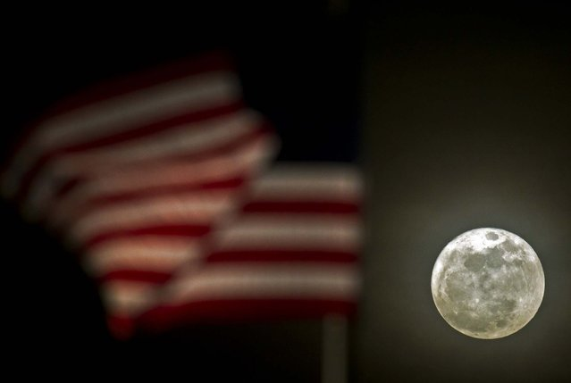 A flag blows in the wind as the moon rises in Brookfield, Wisconsin
