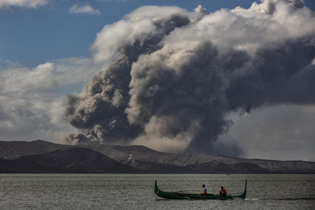 A fishing boat sails along a lake as Taal Volcano erupts on January 14, 2020 in Talisay, Batangas province, Philippines. The Philippine Institute of Volcanology and Seismology raised the alert level to four out of five, warning that a hazardous eruption could take place anytime, as authorities have evacuated tens of thousands of people from the area. An estimated $10 million worth of crops and livestock have been damaged by the on-going eruption, according to the country's agriculture department. (Photo by Ezra Acayan/Getty Images)