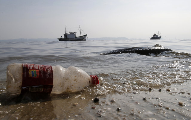 A plastic bottle and a tire are seen near a fishing boat on Fundao beach in the Guanabara Bay in Rio de Janeiro March 13, 2014. (Photo by Sergio Moraes/Reuters)
