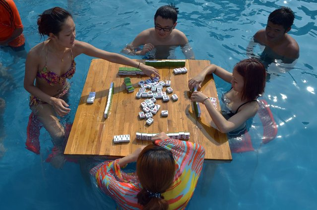 This photo taken on July 9, 2014 shows people playing mahjong as they cool off in a pool inside a waterpark in southwest China's Chongqing municipality. Meteorological department in Chongqing issued an orange alert for high temperature, as the highest temperature rose to more than 37 degrees Celsius and temperature for certain area topped 40 degrees Celsius. (Photo by AFP Photo)