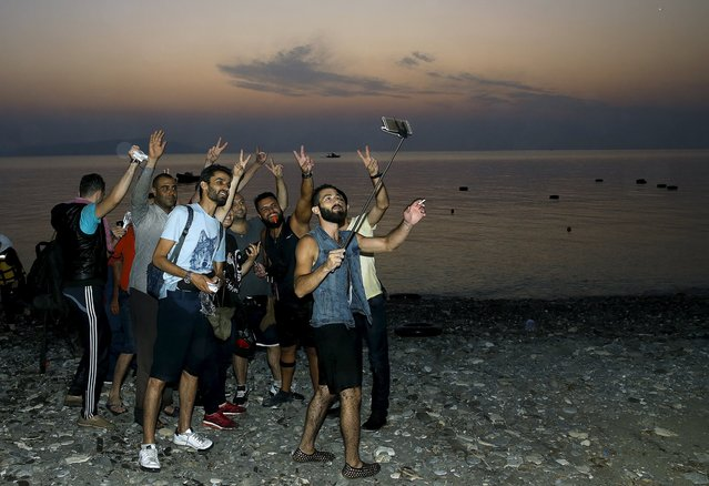 """Syrian refugees take """"selfies"""" moments after arriving on an overcrowded dinghy at a beach on the Greek island of Kos, after crossing a part of the Aegean sea from Turkey, August 9, 2015. United Nations refugee agency (UNHCR) called on Greece to take control of the """"total chaos"""" on Mediterranean islands, where thousands of migrants have landed. About 124,000 have arrived this year by sea, many via Turkey, according to Vincent Cochetel, UNHCR director for Europe. (Photo by Yannis Behrakis/Reuters)"""